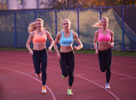 sports training: athlete woman group  running on athletics race track on soccer stadium and representing competition and leadership concept in sport