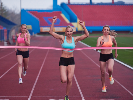 winning race: Female Runners Finishing athletic  Race Together Stock Photo