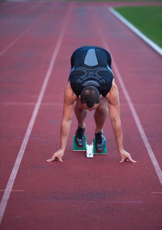 runner: Sprinter leaving starting blocks on the running track. Explosive start. Stock Photo