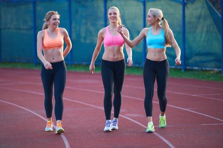 atletismo: atleta mujer grupo de corredores en la pista de atletismo carrera en el estadio de fútbol y que representa la competencia y concepto de liderazgo en el deporte