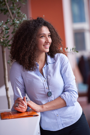 white woman: happy young curly  business woman in the modern office Stock Photo