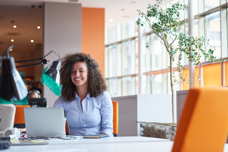 happy young curly  business woman in the modern office Standard-Bild