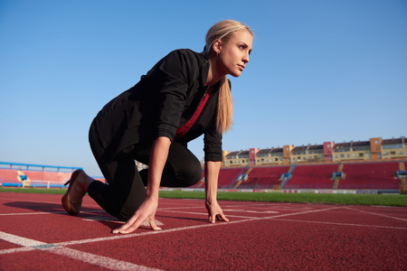 business woman in start position ready to run and sprint on athletics racing track Stock fotó