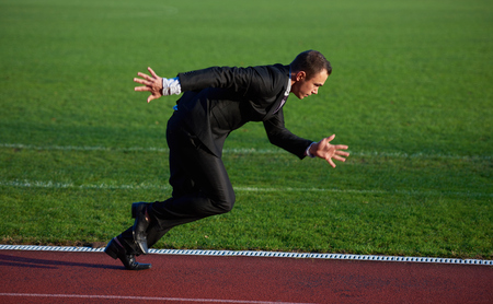 position: business man in start position ready to run and sprint on athletics racing track Stock Photo