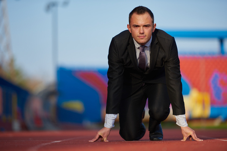 business suit: business man in start position ready to run and sprint on athletics racing track Stock Photo