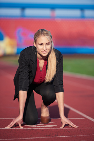 start position: business woman in start position ready to run and sprint on athletics racing track Stock Photo