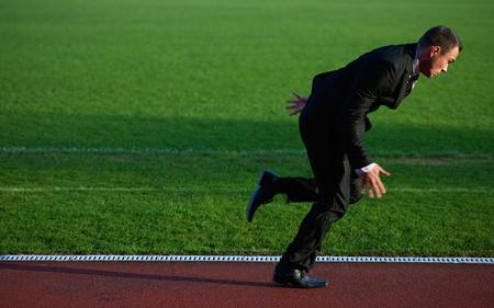 athletics track: business man run and sprint on athletics racing track Stock Photo