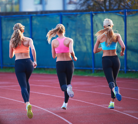 representing: athlete woman group  running on athletics race track on soccer stadium and representing competition and leadership concept in sport