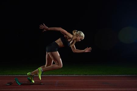 atleta: Mujer velocista dejando la salida de la pista de atletismo. Vista lateral. inicio explosi�n Foto de archivo