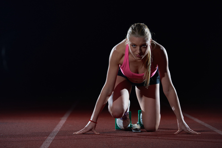 track and field athlete: woman  sprinter leaving starting blocks on the athletic  track. Side view. exploding start