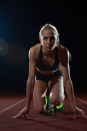 mujer deportista: Mujer velocista dejando la salida de la pista de atletismo. Vista lateral. inicio explosión Foto de archivo