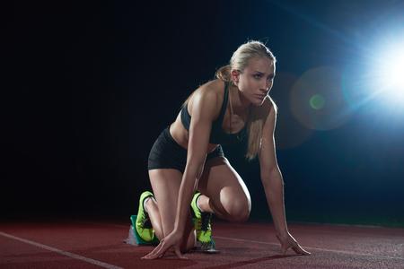 deportista: Mujer velocista dejando la salida de la pista de atletismo. Vista lateral. inicio explosión Foto de archivo