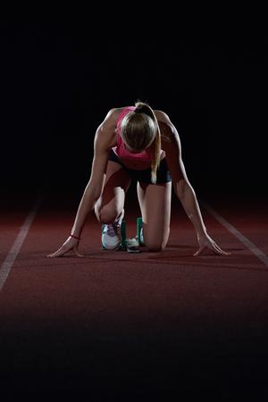 deportistas: Mujer velocista dejando la salida de la pista de atletismo. Vista lateral. inicio explosión Foto de archivo