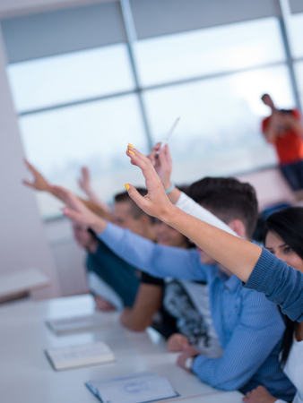 students group raise hands up in classroom