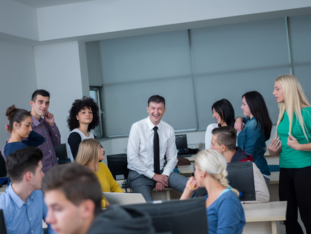 teacher: group of students with teacher in computer lab classrom learrning lessons,  get help and support