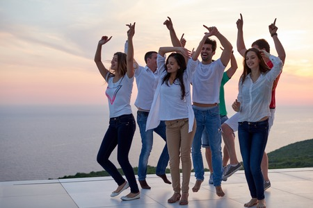 gente bailando: grupo de jóvenes felices bailando y divertirse en la fiesta en la moderna y tocino a casa con la puesta del sol y el océano en el fondo Foto de archivo