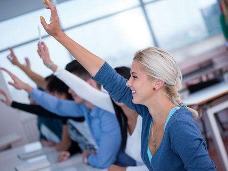 manos levantadas: estudiantes grupo levantan las manos en alto en el aula