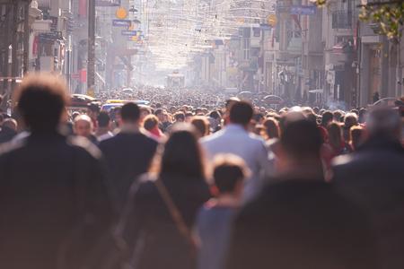 persone: Folla di gente che cammina su una strada trafficata a giorno
