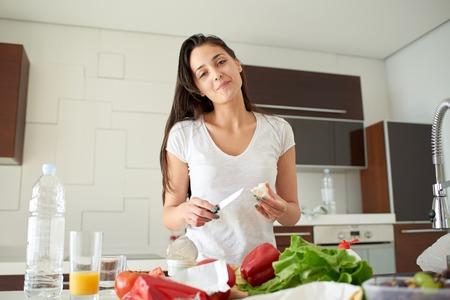 cooking: Mujer joven que cocina en la cocina. Alimentación saludable - ensalada de verduras. Dieta. Concepto de dieta. Estilo de vida saludable. Cocinar en casa. Preparar Comida