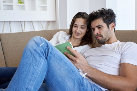 couple couch: romantic relaxed young couple at modern home using tablet computer