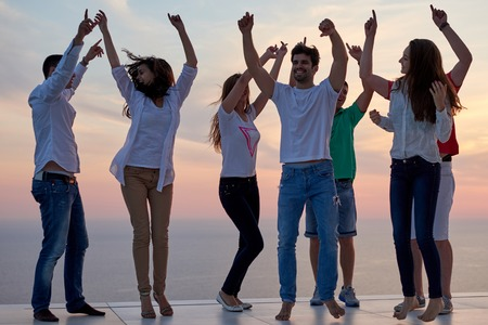 group of happy young people dancing and have fun on party in modern home bacony with sunset and ocean in background Stock Photo