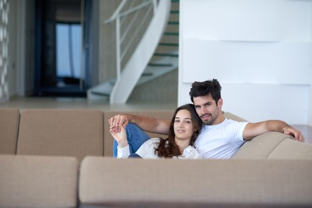 embracing couple: romantic happy young couple relax at modern home staircase indoors Stock Photo