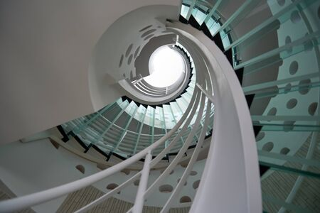 green building: modern glass spiral staircase with metallic hand-rails.