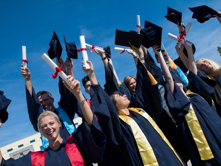 高中学生毕业生扔帽子在蓝天。