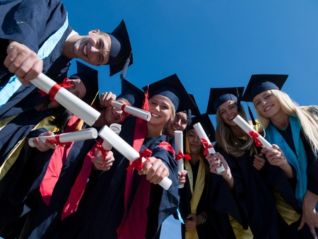 graduation background: high school students graduates tossing up hats over blue sky. Stock Photo