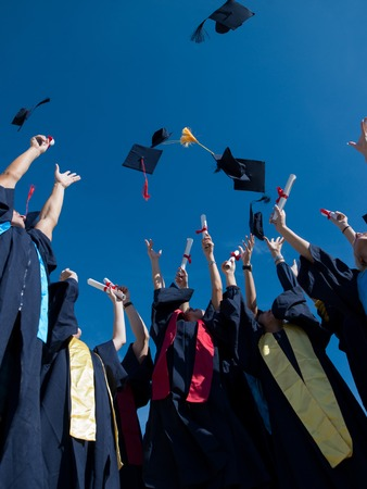 university graduation: high school students graduates tossing up hats over blue sky. Stock Photo
