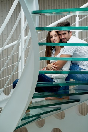 modern home: relaxed young couple on spiral glass stairs in modern home villa indoors