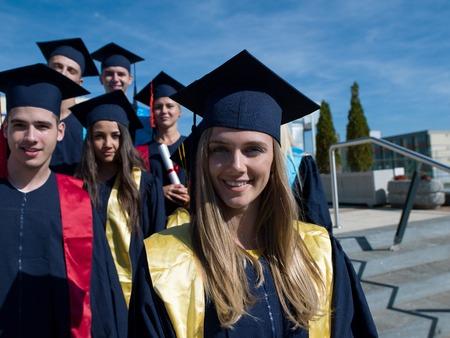 young students: grupo de jóvenes estudiantes de pie en frente del edificio de la universidad el día de graduación graduados