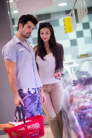 man looking: Young couple shopping in a supermarket