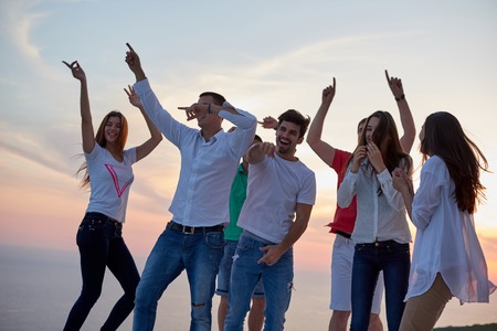 party friends: group of happy young people dancing and have fun on party in modern home bacony with sunset and ocean in background Stock Photo