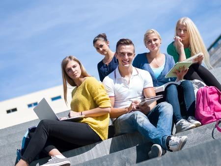 Groep portret van gelukkige studenten buiten het zitten op de trappen hebben plezier Stockfoto