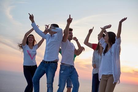 幸せな若者のグループの人々 のダンスと夕日と現代の家でのパーティーと背景の海に楽しく