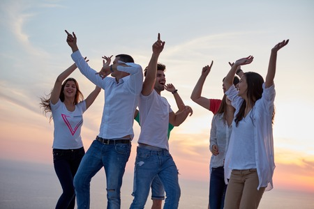 group of happy young people dancing and have fun on party in modern home bacony with sunset and ocean in background Standard-Bild