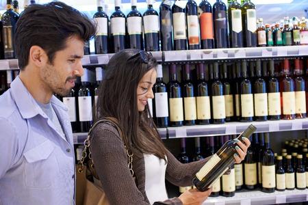 tomando vino: Pareja joven de compras en un supermercado