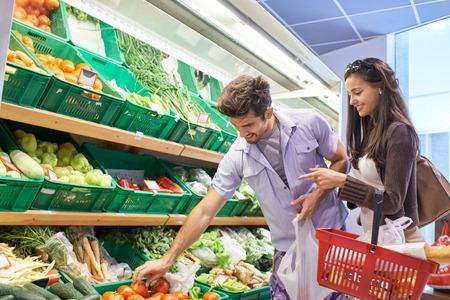 alimentos y bebidas: Pareja joven de compras en un supermercado