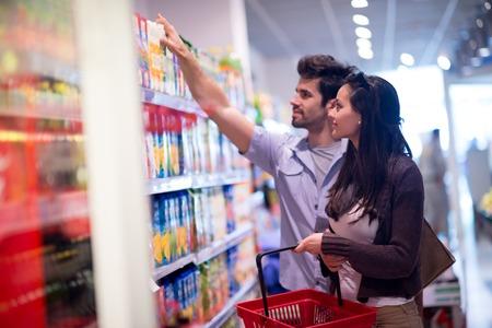 comprando: Pareja joven de compras en un supermercado