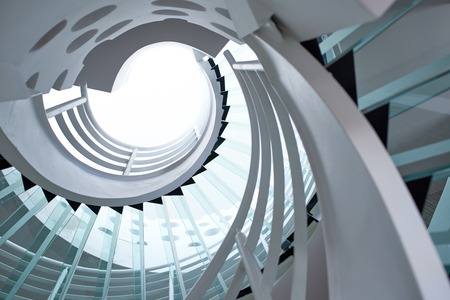 spiral staircase: modern glass spiral staircase with metallic hand-rails.