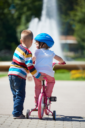 outdoor exercise: Happy childrens outdoor,  brother and sister in park have fun. Boy and girl in park learning to ride a bike.