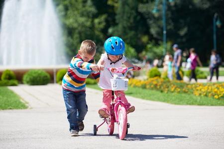 kinder spielen: Glückliche Kinder im Freien, Bruder und Schwester im Park Spaß haben. Jungen und Mädchen im Park Lernen, ein Fahrrad zu reiten.