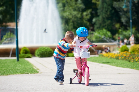 sister: Happy childrens outdoor,  brother and sister in park have fun. Boy and girl in park learning to ride a bike.