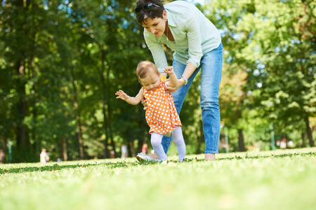 step daughter: happy mother and baby child in park making first steps .  Walking and hugging.