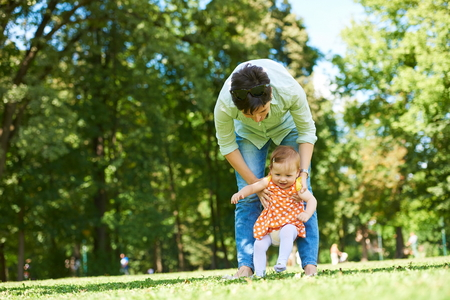 children learning: happy mother and baby child in park making first steps .  Walking and hugging.