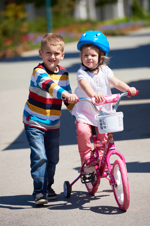 toddler boy: Happy childrens outdoor,  brother and sister in park have fun. Boy and girl in park learning to ride a bike.