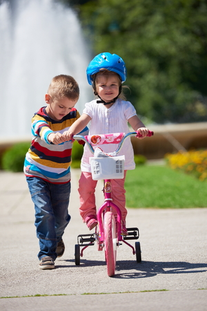 brother: Happy childrens outdoor,  brother and sister in park have fun. Boy and girl in park learning to ride a bike.