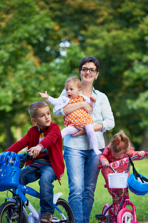 busy: Family portrait outdoor in park. Modern mom with kids. Child learning to ride bike Stock Photo