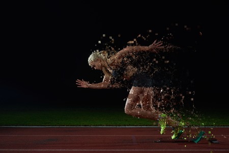 athletics track: pixelated design of woman  sprinter leaving starting blocks on the athletic  track. Side view. exploding start Stock Photo
